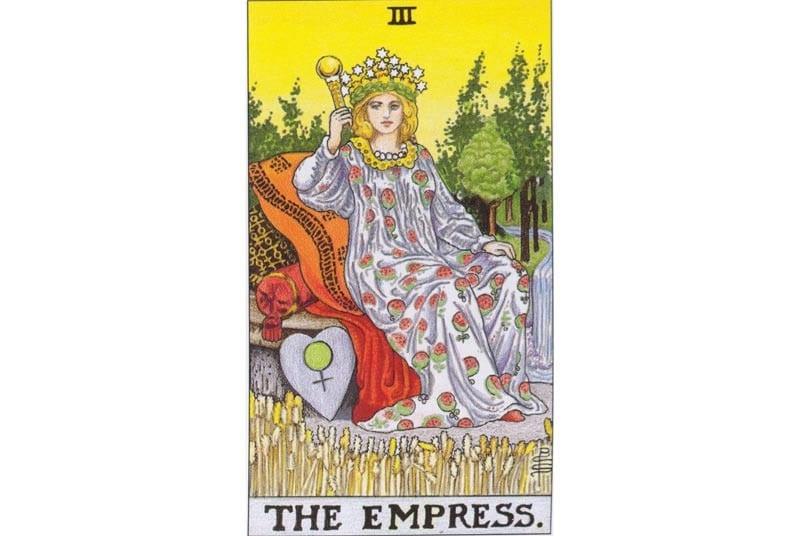 Lá The Empress (Nữ hoàng) của bộ Rider Waite Tarot có người đàn bà mặc áo lựu đỏ (lựu tượng trưng cho hoa quả của đất mẹ và sự nữ tính), giữa vườn cây trái màu mỡ, có cái khiên với dấu hiệu Venus.
